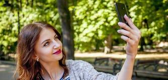 Auto-temps Portrait de jeune femme heureuse d'intoxiqué de selfie photo stock