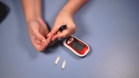 Auto-test per diabete Donna che fa la prova della glicemia stock footage