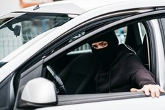 Auto thief in black balaclava closing door of stolen car Royalty Free Stock Image