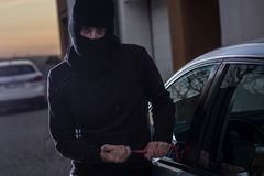Auto thief in black balaclava trying to break into car Stock Image