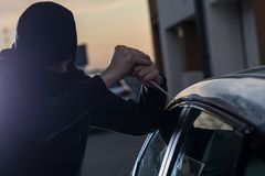 Auto thief in black balaclava trying to break into car. With screwdriver. Car thief, car theft Stock Images