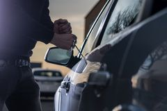 Auto thief in black balaclava trying to break into car. With screwdriver. Car thief, car theft royalty free stock photography