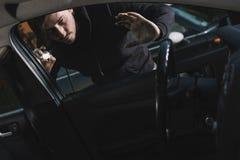 Auto thief looking to car interior Royalty Free Stock Image