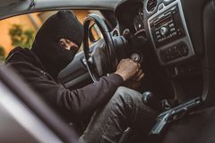 Auto thief trying to start car with screwdriver in ignition Royalty Free Stock Photo