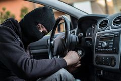 Auto thief trying to start car with screwdriver in ignition Royalty Free Stock Image