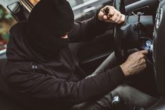 Auto thief trying to start car with screwdriver in ignition. Car thief trying to start car with screwdriver in ignition. Car thief, car theft Stock Photo