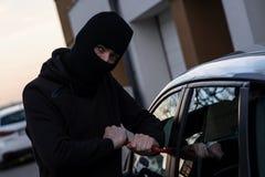 Auto tjuv i den svarta balaclavaen som försöker att bryta in i bilen royaltyfri fotografi