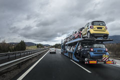 Auto transporter laden by small cars is on the highway Stock Photos