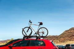 Auto transportiert Fahrrad auf dem Dach Lizenzfreie Stockfotos