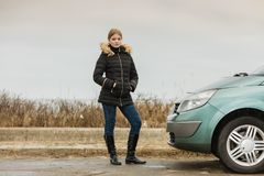 Blonde driver woman standing next to car. Auto traveling concept. Blonde driver woman in winter clothes standing next to her car Stock Photo