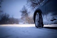 Auto und fallender Schnee im Winter auf Waldweg Stockfotografie
