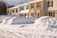 Auto und Häuser nach Schneesturm Stockbilder
