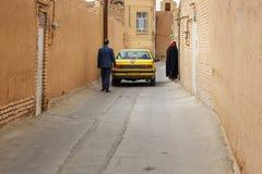 Auto und iranische Leute auf der schmalen Straße der alten Stadt in Yazd iran Stockfotografie