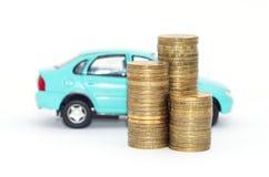 Auto und Münzen auf einem weißen Hintergrund Stockfotografie
