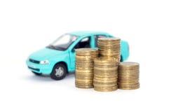 Auto und Münzen auf einem weißen Hintergrund Stockbild