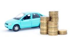 Auto und Münzen auf einem weißen Hintergrund Lizenzfreie Stockbilder