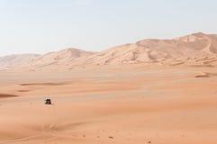 Auto unter Sanddünen in Oman-Wüste (Oman) lizenzfreies stockfoto