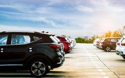 Auto van luxe de zwarte, witte en rode nieuwe die suv op concreet parkeerterrein bij fabriek met blauwe hemel en wolken wordt gep Stock Afbeeldingen