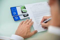 Auto-Verkaufsvertragform des Geschäftsmannes füllende lizenzfreie stockfotos
