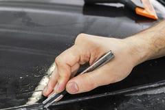 Auto verpakkende specialist die vinylfolie of film op auto snijden Beschermende film op de auto Het toepassen van een beschermend stock fotografie