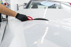 Auto verpakkende specialist die vinylfolie of film op auto zetten Beschermende film op de auto Het toepassen van een beschermende stock afbeeldingen