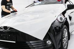 Auto verpakkende specialist die vinylfolie of film op auto zetten Beschermende film op de auto Het toepassen van een beschermende royalty-vrije stock afbeelding