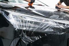 Auto verpakkende specialist die vinylfolie of film op auto zetten Beschermende film op de auto Het toepassen van een beschermende stock afbeelding