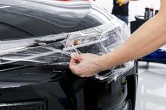 Auto verpakkende specialist die vinylfolie of film op auto zetten Beschermende film Het toepassen van een beschermende film met h stock foto