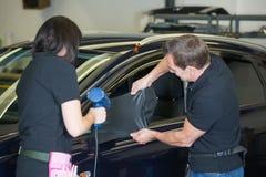 Auto verpakkende specialisten die zijspiegel met koolstoffolie verpakken Stock Afbeeldingen