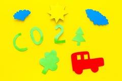 Auto verunreinigt die Umwelt durch Kohlendioxyd Auto, Umwelt und CO2-Ausschnitt auf Draufsicht des gelben Hintergrundes Lizenzfreie Stockfotos