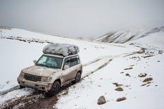 Auto von Reisenden auf Gebirgsschnee-Straßenlandschaft Auto des Jeeps 4x4 auf einem Gebirgspass, Bergspitze Extremes gefährliches Lizenzfreie Stockbilder