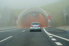 Auto vor Tunnel auf nebeliger Straße Stockfotos