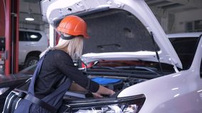 Auto-Werkstatt, Frauenmechaniker in Sturzhelm und Overall, der defektes Auto mit offener Haube in der Tankstelle repariert stock video