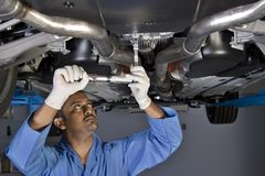 Auto werktuigkundige onder auto Stock Foto
