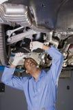 Auto werktuigkundige onder auto Stock Fotografie