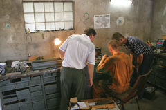 At auto workshop. Three man in auto workshop looking on something. A lot of spares around them Stock Image