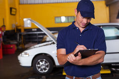Auto workshop manager. Male auto workshop manager writing on clipboard at the repair shop Stock Images