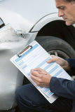 Auto Workshop Mechanic Inspecting Damage To Car And Filling In R Stock Photography