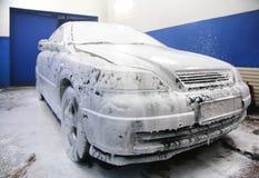 Auto in zeepsop bij de was royalty-vrije stock afbeelding
