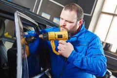 Autoabtönen Kraftfahrzeugmechanikertechniker, der Folie anwendet stockfotografie