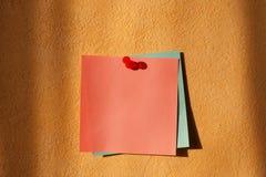 Autoadesivi di colore su una parete arancione Fotografia Stock Libera da Diritti
