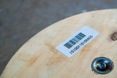 Autoadesivo del codice a barre sul ruolo di legno Fotografie Stock