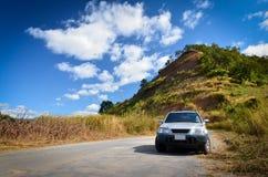 Autoanschlag auf Hügel unter dem schönen Himmel Stockfoto