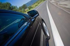 Autoauf eine Straße schnell antreiben Lizenzfreie Stockfotografie