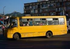 Autobús amarillo apretado en la calle en abajo la ciudad Batumi por la tarde caliente de julio Fotografía de archivo
