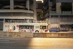 Autobús de dos plantas turístico con paseos de los pasajeros a través de las calles de la ciudad en los rayos del sol poniente foto de archivo