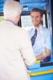 Autobús del embarque del hombre mayor y boleto de la compra Imagen de archivo libre de regalías