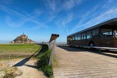Autobús en el camino a la abadía famosa de Mont Saint Michel Es una de las atracciones turísticas más famosas de Francia Foto del Imágenes de archivo libres de regalías