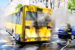Autobús en el fuego en la calle en la mitad del día Foto de archivo