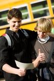 Autobús escolar: Adolescente elegante consigue el buen boletín de notas Imagen de archivo libre de regalías